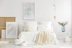 White minimalist master bedroom interior. World cities map posters in a white minimalist master bedroom interior with scandinavian design furniture and stock image