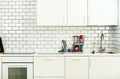 White minimalistic kitchen interior and design. Tile wall background. Household appliances - blender, vacuum machine. Modern stove, dishwasher, oven, table Royalty Free Stock Images