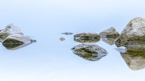 White misty day rocks reflection