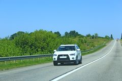 White Mitsubishi Outlander going on asphalted road. Traveling concept stock images