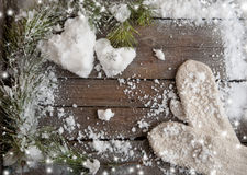 White mittens and snow hearts on a wooden plank background with copy space Royalty Free Stock Photography