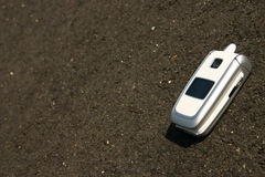 White mobile cell phone on a road. Showing the white line Royalty Free Stock Photos