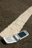 White mobile cell phone on a road. Showing the white line Stock Image