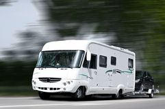 White mobile home. A mobil home towing a black car Stock Images