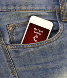 White mobile phone with call from my love in jeans pocket Royalty Free Stock Photo