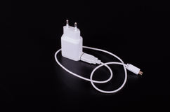 White mobile phone charger on black background Stock Images