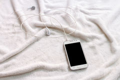 White mobile phone with headphones on a towel Stock Photography