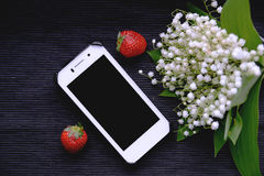 White mobile phone and lily of the valley. Bouquet Stock Photo