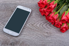 White mobile phone and roses on a wooden background Stock Photo