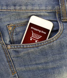 White mobile phone with shopping cart in jeans pocket Stock Images