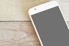 White mobile on a wooden desk from above. Empty screen for mock up and empty copy space. For Editor`s text royalty free stock image