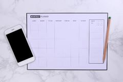 White mock up smartphone and planner schedule on marble backgroun. White mockup smartphone and planner schedule on marble background Royalty Free Stock Images