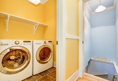 White Modern appliances in small yellow laundry room Royalty Free Stock Image