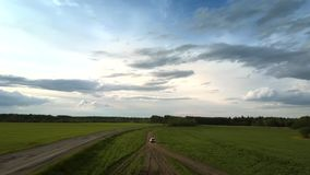 White modern car drives along ground road near field. And parallel asphalt way under cloudy dark sky round aerial motion. Concept abandoned road nature stock footage