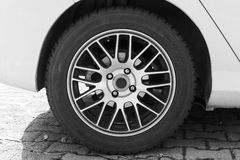 White modern car fragment with wheel on steel disc Royalty Free Stock Photo