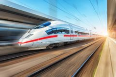 White modern high speed train in motion on railway station. At sunset. Passenger train on railroad track with motion blur effect in Europe. Railway platform royalty free stock photos
