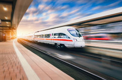 White modern high speed train in motion. On railway station at sunset. Train on railroad track with motion blur effect in Europe in evening. Railway platform royalty free stock images