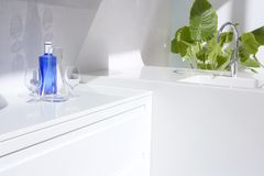 White modern kitchen, blue water bottle and plants. White modern kitchen detail, blue water bottle and green plants Royalty Free Stock Images