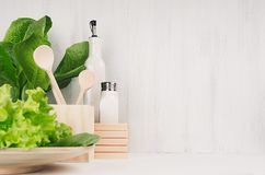 White modern kitchen decor with beige natural wooden dish, utensils, fresh green salad on wood background. royalty free stock photo