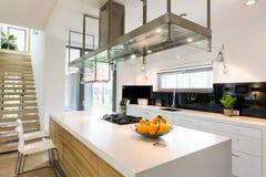 White modern kitchen. In spacious trendy house design Royalty Free Stock Photo