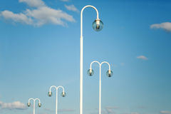 White modern lamp posts against blue sky Royalty Free Stock Photography