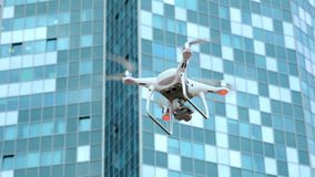 White modern quadcopter flies and shoots video in the city, against the backdrop of an industrial business building