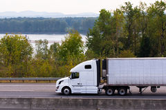 White modern semi truck with reefer on highway along river Colum Royalty Free Stock Image