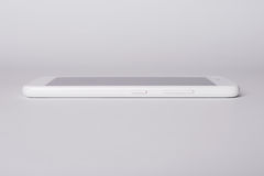 White modern smartphone with blank screen lies on the surface, isolated on white background. Elements Stock Image