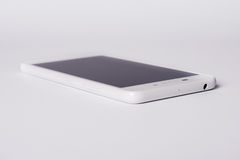 White modern smartphone with blank screen lies on the surface, isolated on white background. Stock Photography