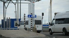 White Modern Vans Drive Through Checkpoint with Barriers