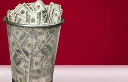 Money in trash bin on light background