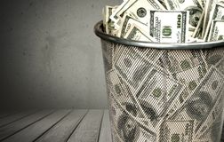 Money in trash bin on wooden background. White money isolated business financial success risk Stock Photography