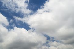 White cumulus clouds under bright blue sky Stock Photos