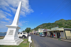 White monument with row of shops with old cowboy design building at Levuka, Ovalau island, Fiji royalty free stock photo