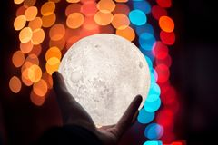 White moon in hand on blured bokeh backround in dark room. stock image