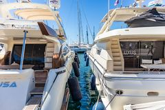 White moored luxury yachts with masts, in contrast to blue calm sea. Reflection of vessels, sky background, close up view. April 29, 2019. Marina Zeas in Piraeus stock photos