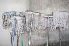 White mops lean against white wall Stock Images