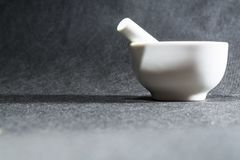 White mortar with a pestle from porcelain. A drinking bowl for crushing of spices. Black background. Kitchen utensils. Ware. stock photo