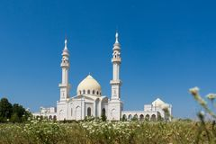 White mosque on blue sky background. White mosque against blue sky and white flowers. The mosque building with towers and a beautiful dome Stock Image
