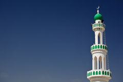 White mosque with minaret against blue sky Stock Photo
