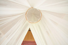 White mosquito net over a bed in a luxurious hotel Stock Image