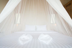 White mosquito net over a bed in a luxurious hotel Royalty Free Stock Photo