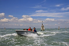 White motor boat with passengers in Venetian lagoon in Venice, Italy Stock Images