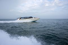 A white motor boat rushes through the blue sea. THAILAND - JANUARY: Tourists sail from the island to the island by boat, as part of an ordinary excursion, in Stock Photos