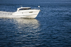 White motor boat sailing in calm water. Image of a white motor boat sailing in calm water on a sunny day Royalty Free Stock Image