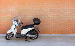 White Motor Scooter against a Brick Wall Stock Image