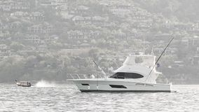 White motor yacht anchored in calm clean sea with modern buildings on background stock footage