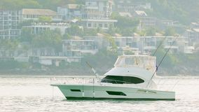 White motor yacht anchored in calm clean sea with modern buildings on background Stock Photo