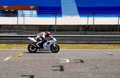 White Motorcycle, Start Line Markings, Motor Sports. White yamaha motorcycle passing through the start line markings. Empty stands from Estoril Circuit Royalty Free Stock Photos