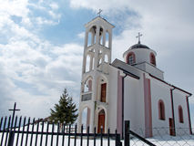 White mountain church in snow against white clouds Stock Images